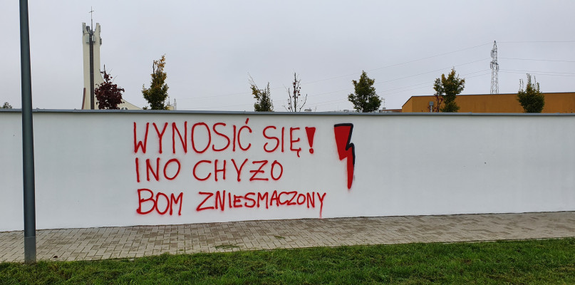 Napis na murze szkoły specjalnej, a obok powstaje mural. - Ręce opadają  - Zdjęcie główne